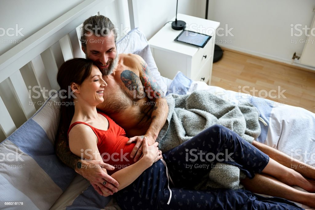 Loving pregnant couple together on bed stock photo