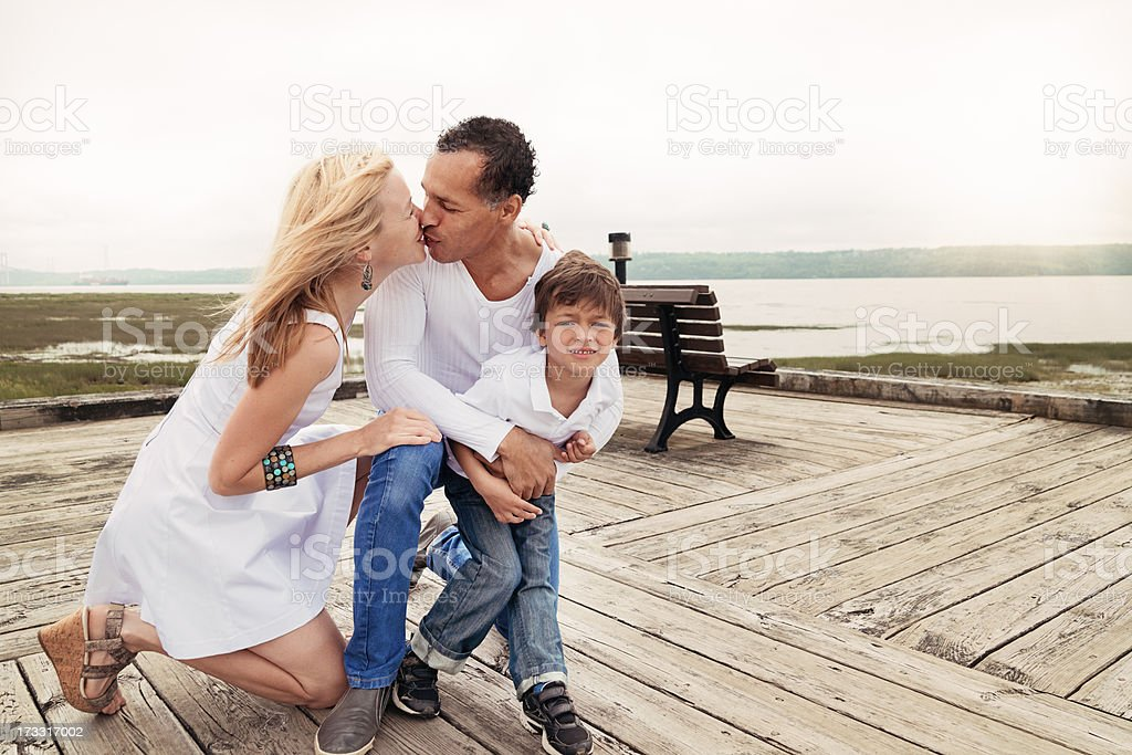Loving real interracial family on a pier in summer. royalty-free stock photo
