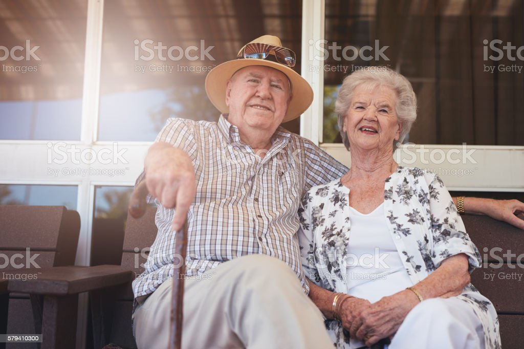 Loving retired couple relaxing on a bench outside their house stock photo