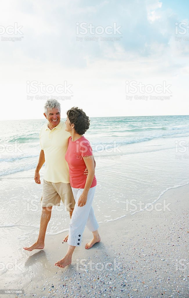 Loving retired couple with arms around walking on a beach royalty-free stock photo