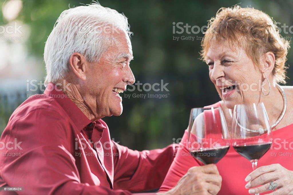 Loving senior couple drinking red wine, talking stock photo
