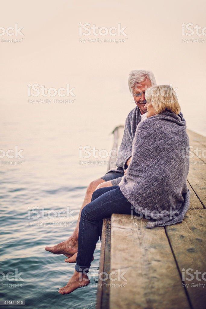 Loving senior couple enjoying the sunrise stock photo