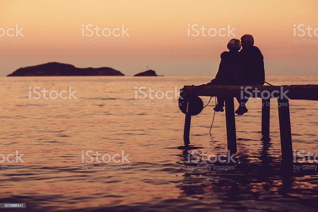 Loving senior couple enjoying the sunset stock photo