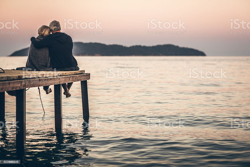 Loving senior couple enjoying the sunset stock photo