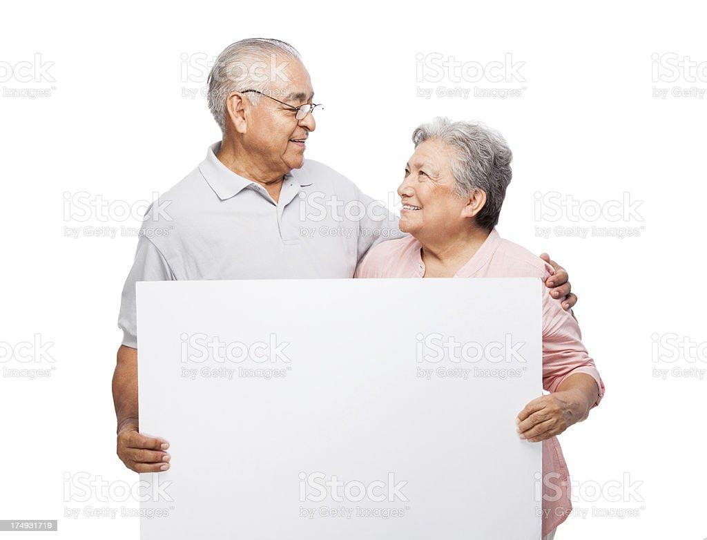 Loving senior couple holding a sign stock photo