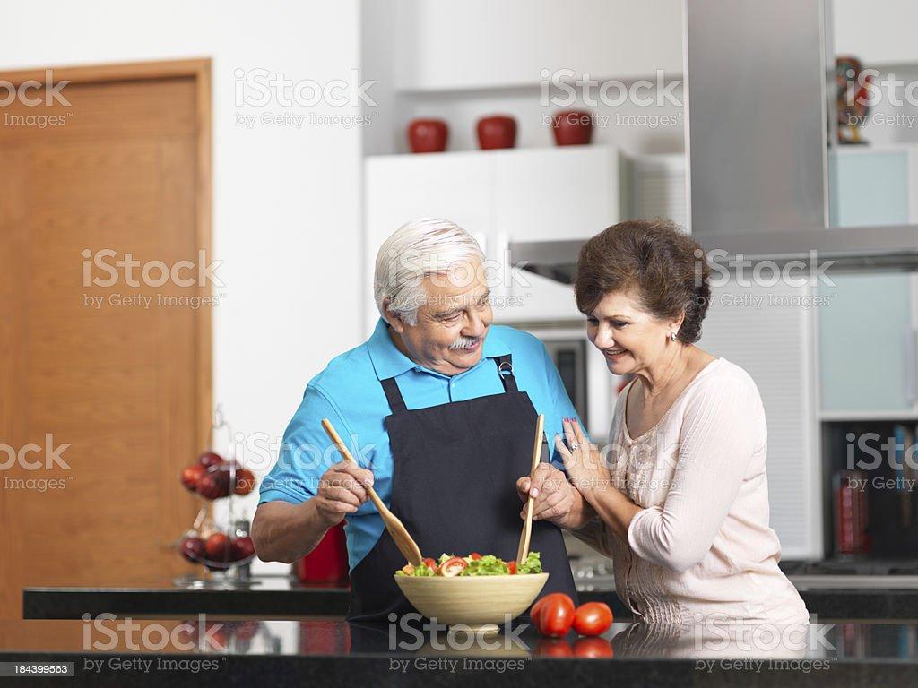 Loving senior couple preparing a healthy salad stock photo
