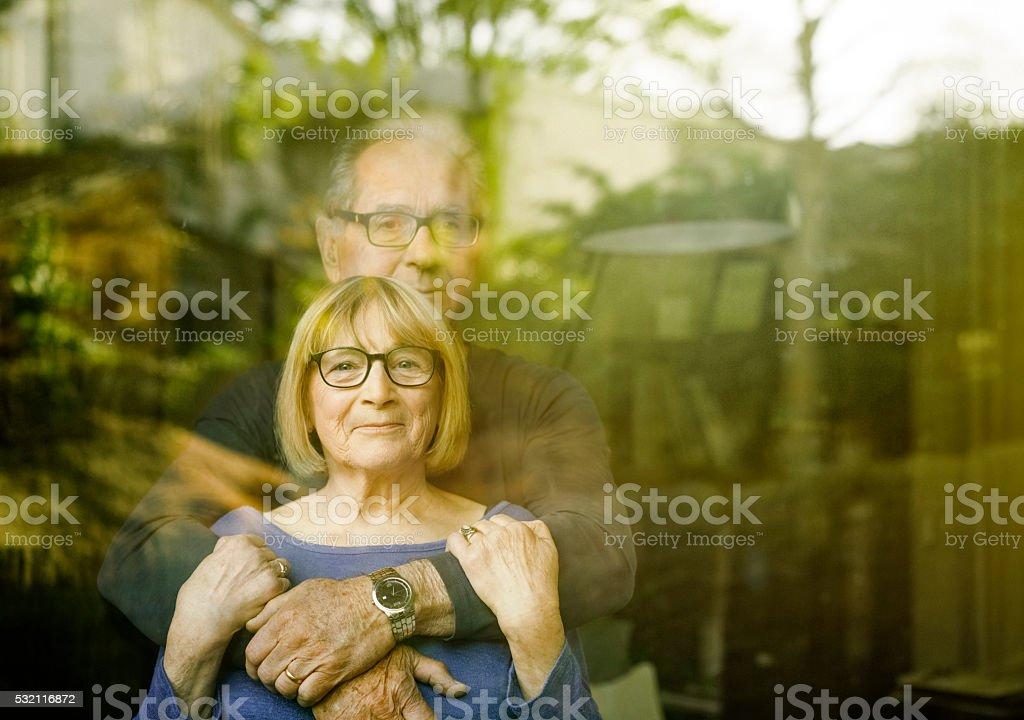Loving senior couple seen through glass window stock photo