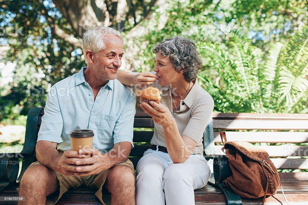 Loving senior couple sitting on a park bench stock photo