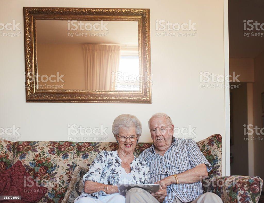 Loving senior couple using digital tablet at home stock photo