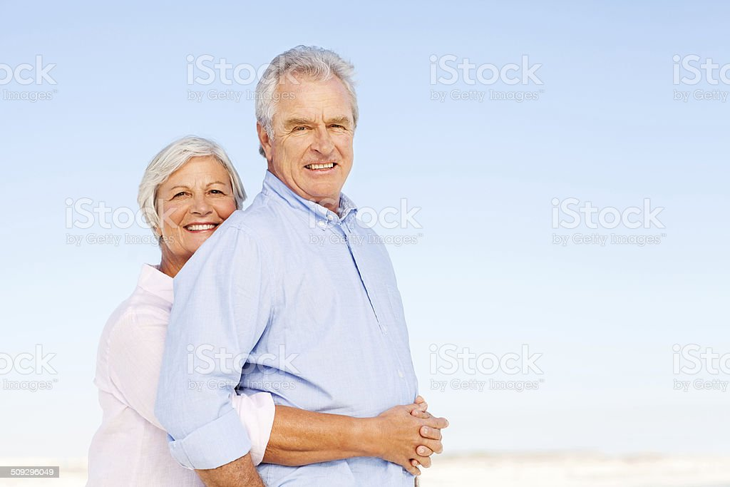 Loving Senior Woman Embracing Man From Behind Against Clear Blue royalty-free stock photo