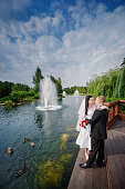 loving wedding couple standing and kissing near water