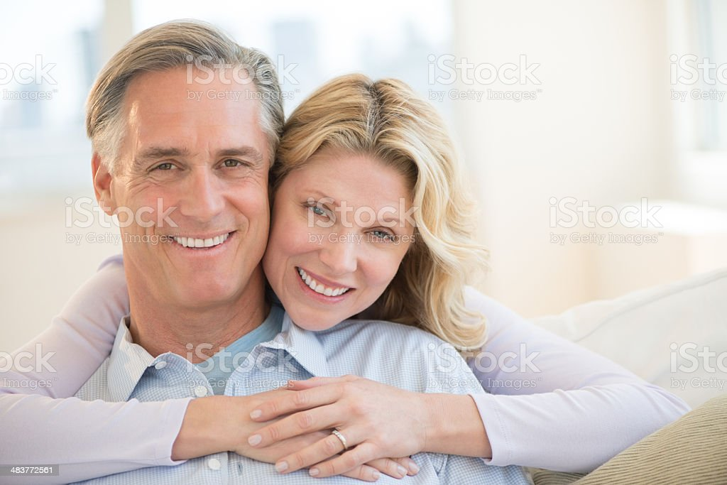Loving Woman Embracing Man From Behind At Home royalty-free stock photo