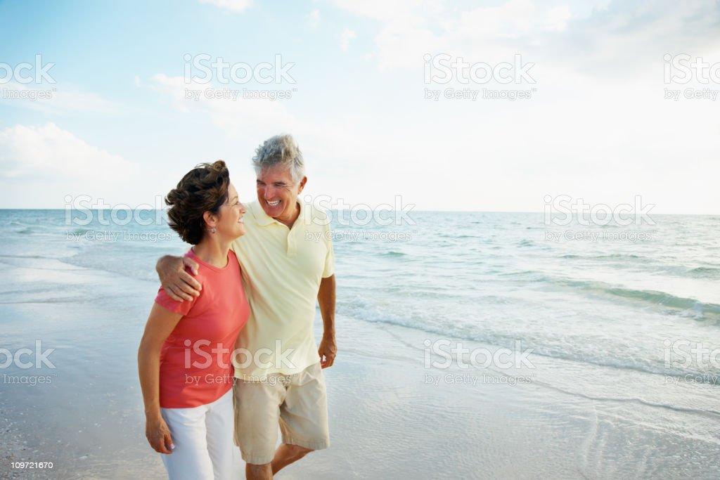 Loving woman hugging  senior man on a beach royalty-free stock photo