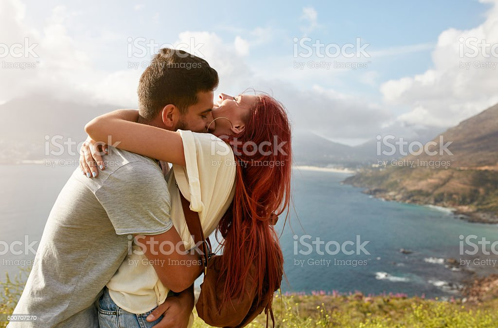 Loving young couple embracing outdoors stock photo