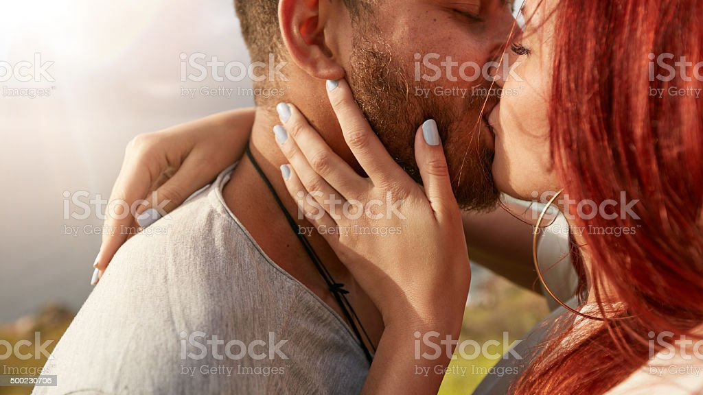 Loving young couple kissing outdoors stock photo