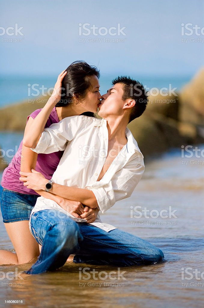 loving young couple kissing while squating by the beach royalty-free stock photo