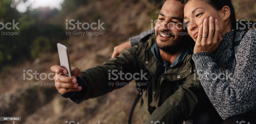 Loving young couple on hike taking a selfie stock photo