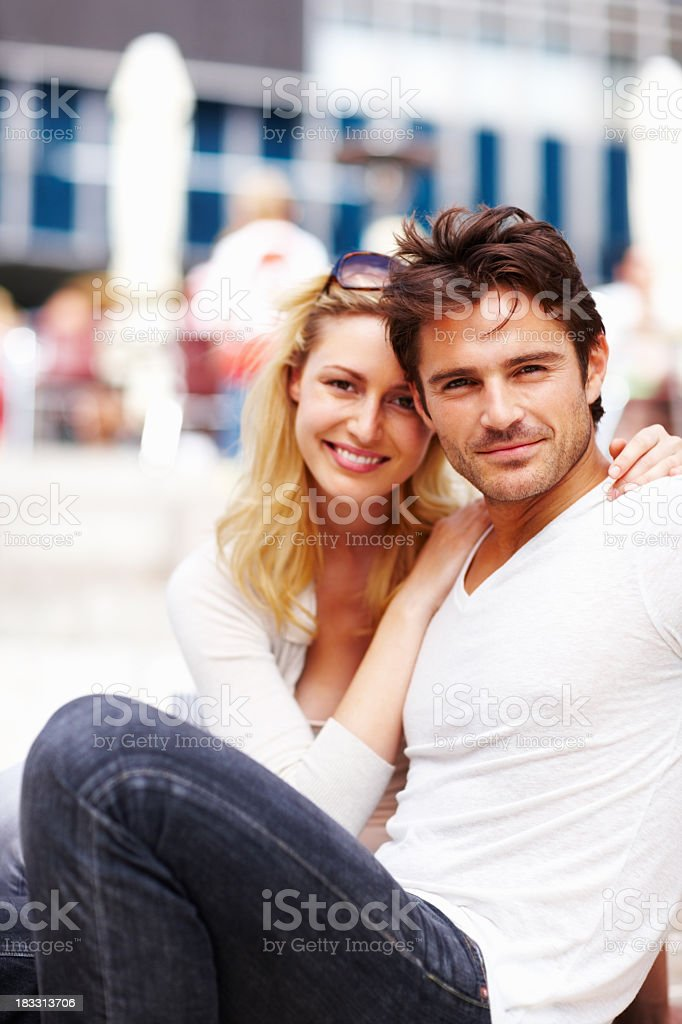Loving, young couple sitting together and smiling royalty-free stock photo