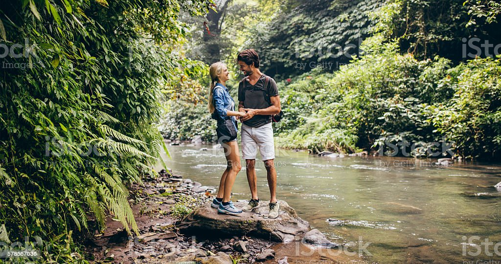 Loving young couple standing by mountain stream stock photo
