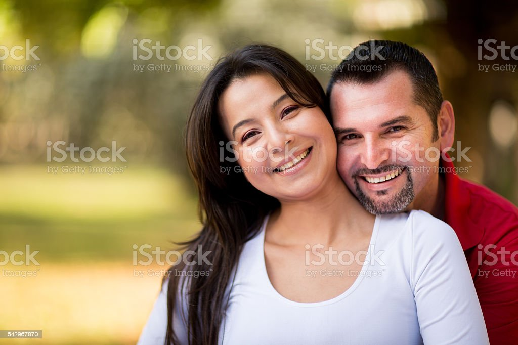 Loving young latin couple smiling at camera stock photo