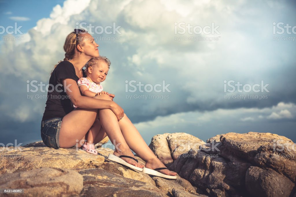 Loving young mother embrace her baby sitting on rocks with dramatic sky and clouds on background during sunset with copy space stock photo