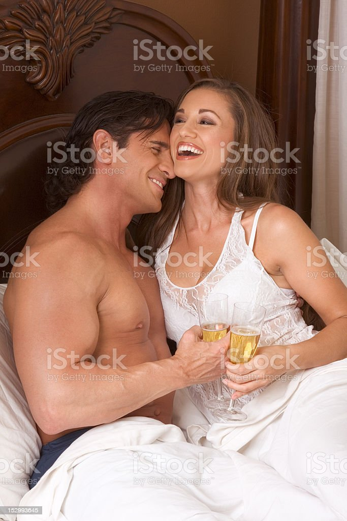 Loving young sensual couple with Champagne in bed royalty-free stock photo