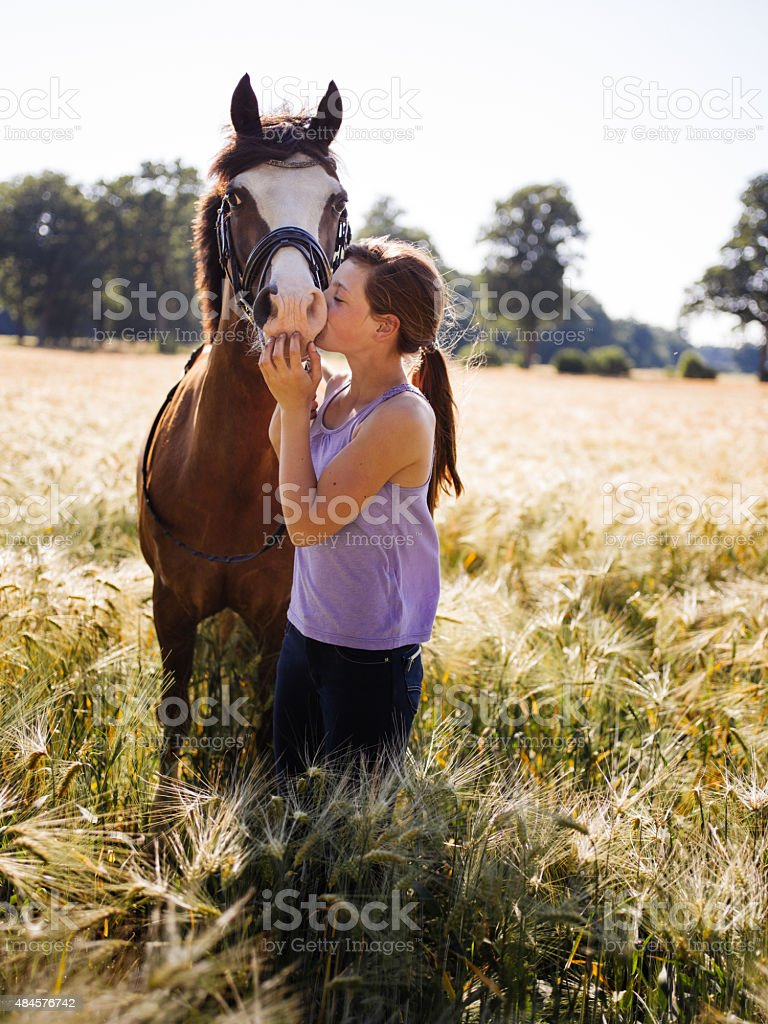 Lovingly girl giving her horse a kiss on it's nose stock photo