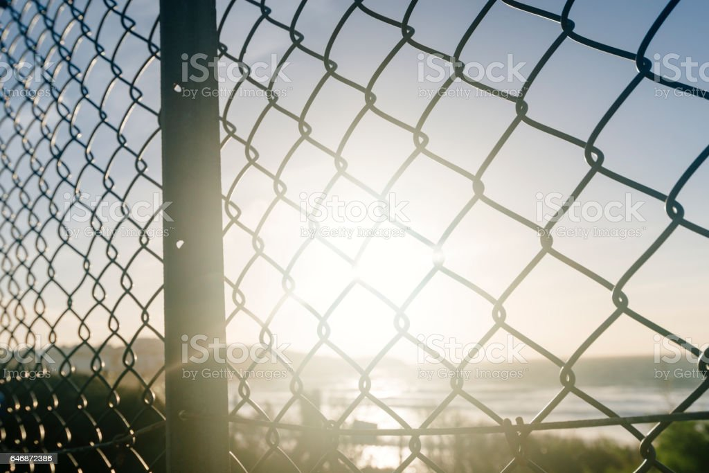 Low afternoon flaring Sunshine through metal fencing, Fistral Beach, Newquay stock photo