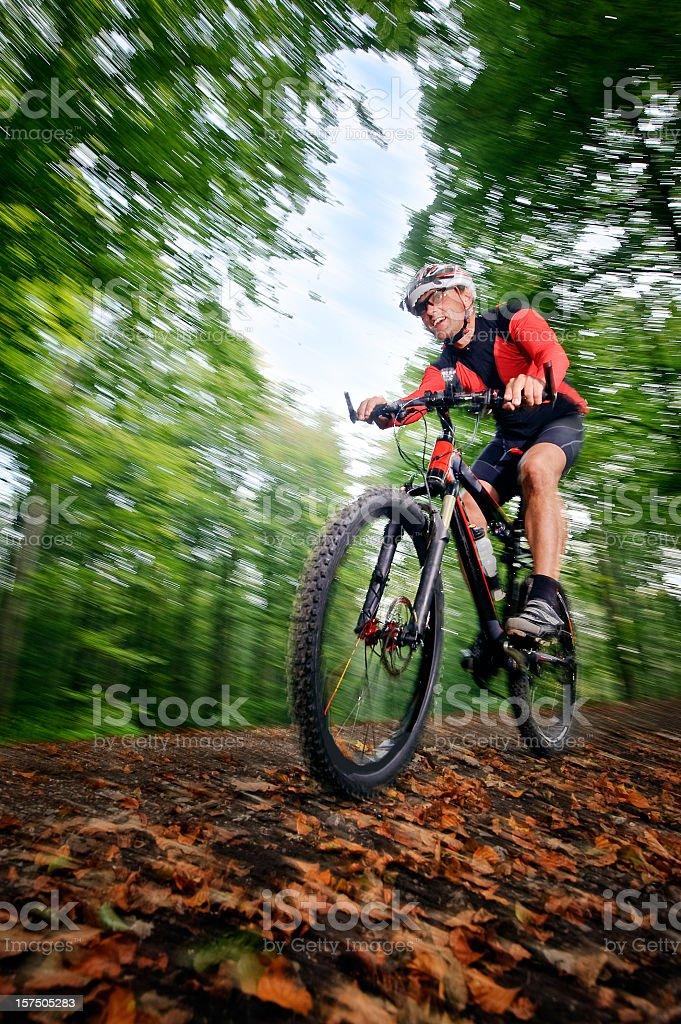 Low angle blurred view of man with a helmet mountain biking royalty-free stock photo
