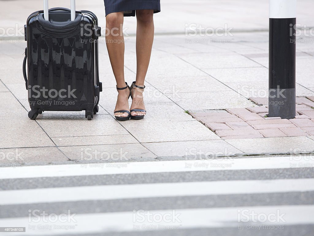 Low angle business woman waiting on sidewalk stock photo