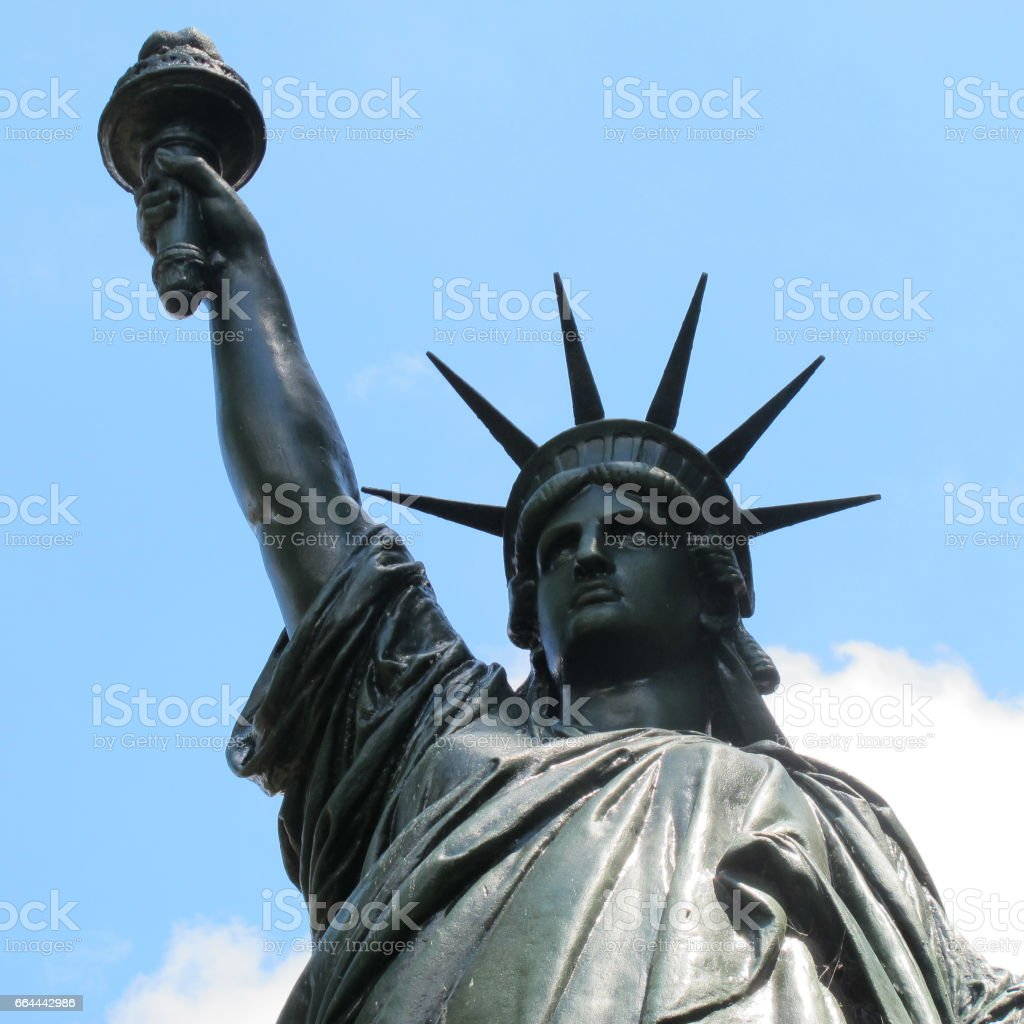 Low angle closeup of the Liberty Statue, blue sky at background stock photo