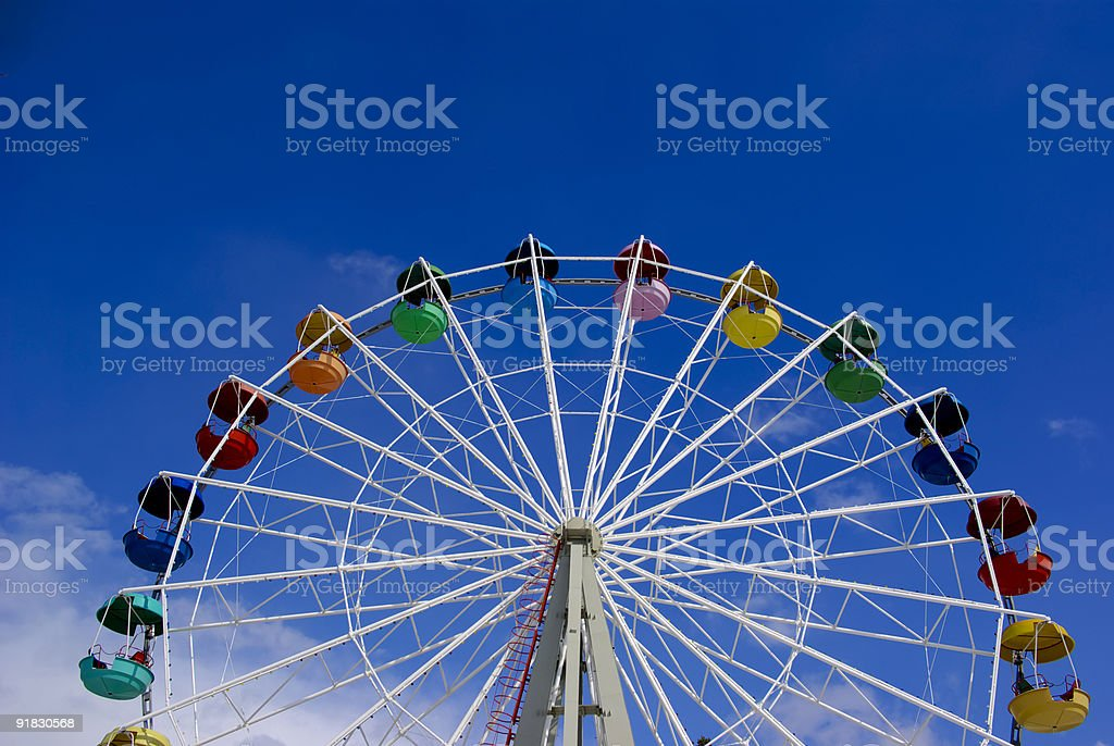 Low angle image of a Ferris wheel against a blue sky stock photo