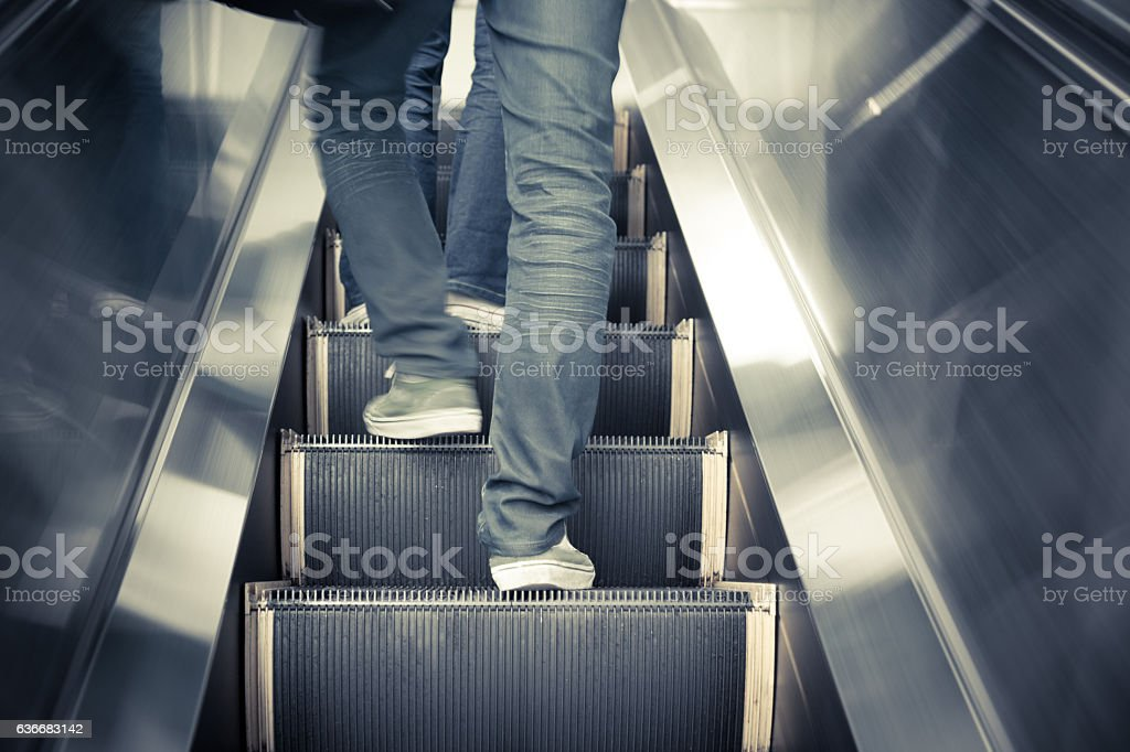Low angle male feet walking in sneakers up escalator. stock photo