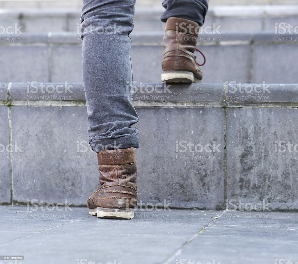 Low angle man walking up steps stock photo