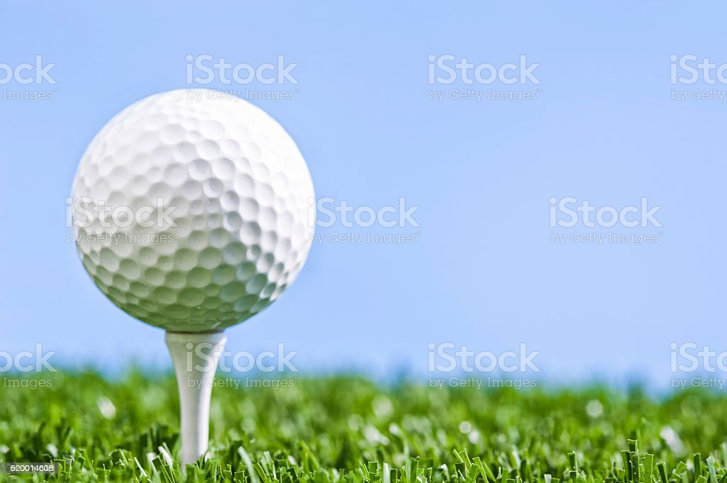 A low angle view of a Golf ball sitting on white wooden tee against a...