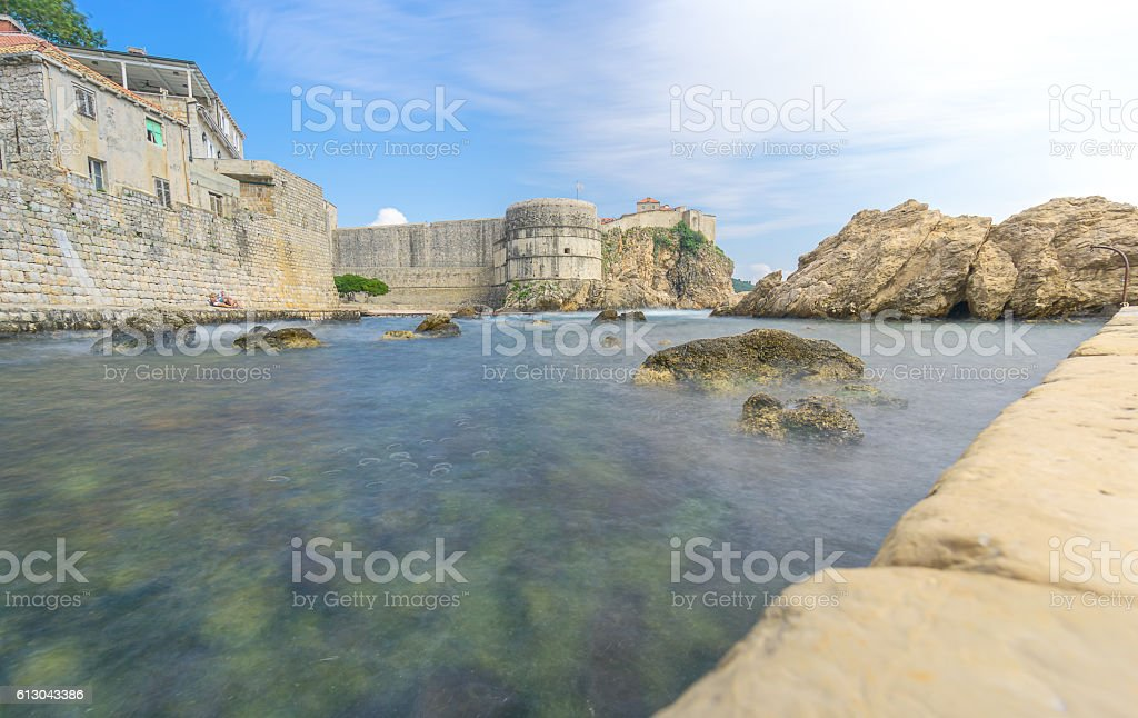 Low Angle of Dubrovnik's City Walls with Sunbathers stock photo