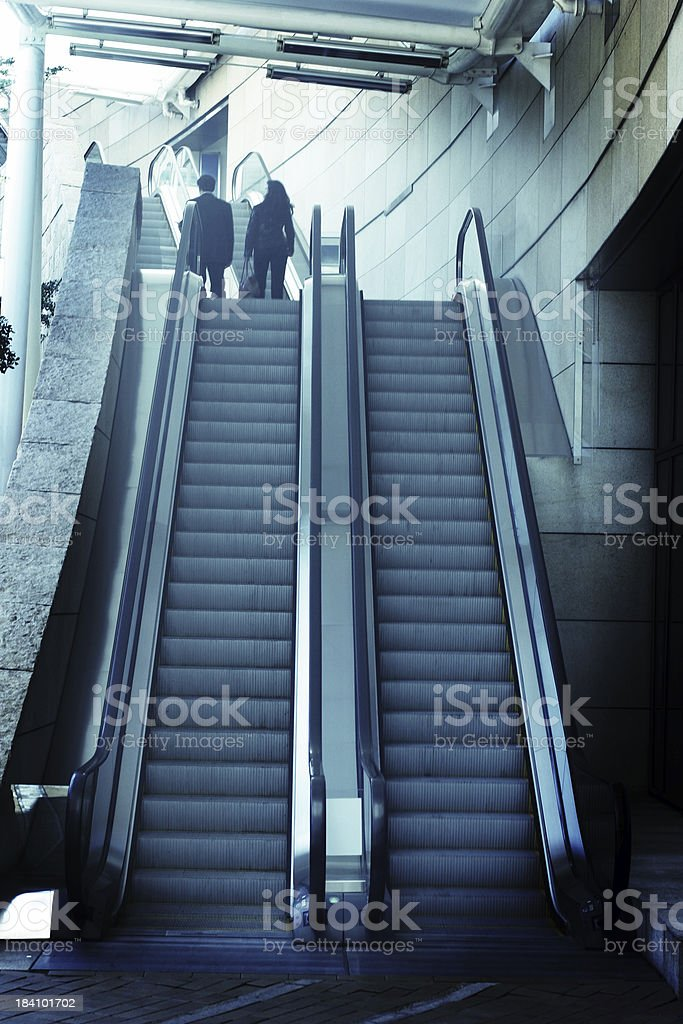 Low Angle of Escalator with Two Business Executives in Suit stock photo