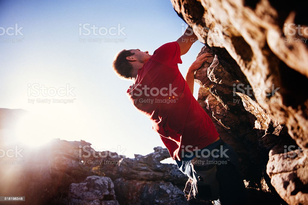 Low angle of extreme free climbing man hanging on rock stock photo