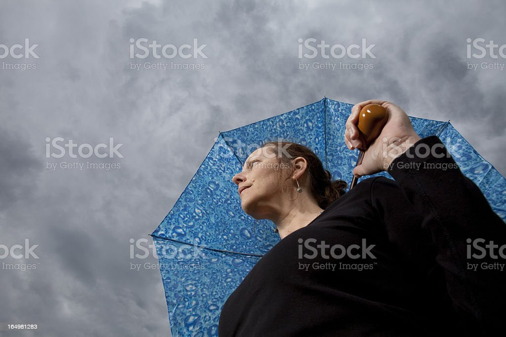 Low angle of woman with umbrella looking at stormy weather stock photo