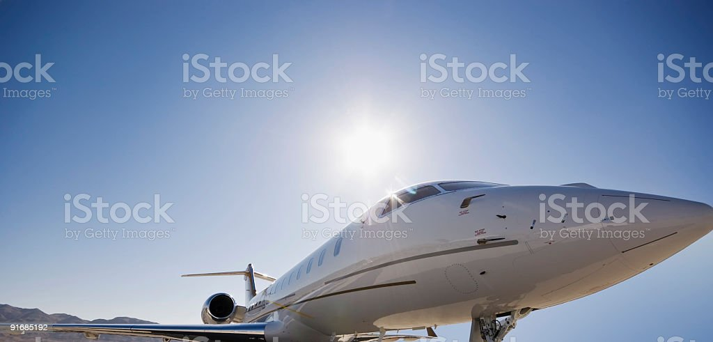 Low angle shot of personal jet with background hills and sun stock photo