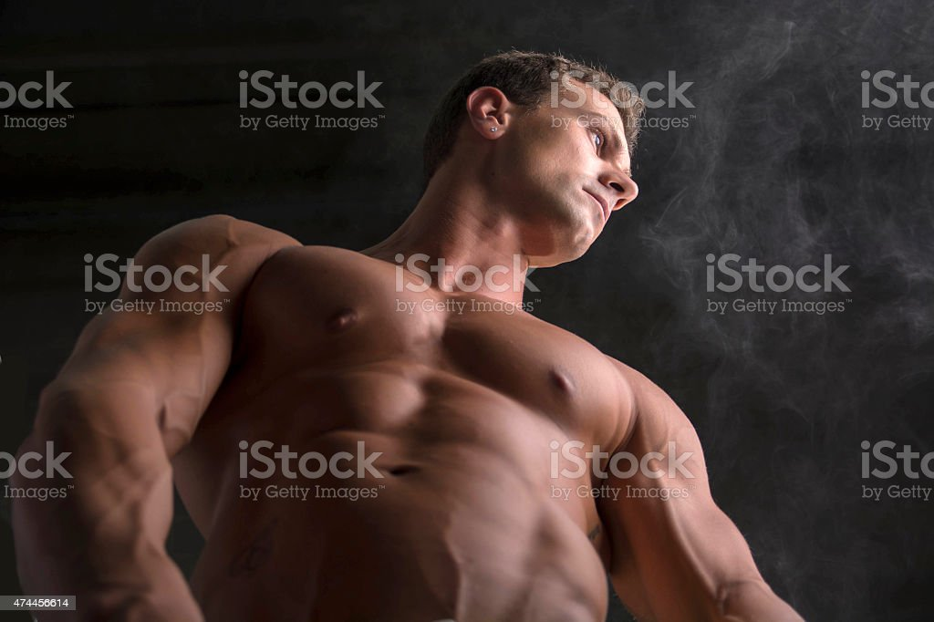 Low angle shot of shirtless male bodybuilder on dark background stock photo