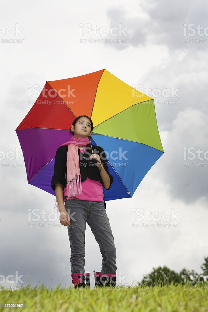 Low angle shot of teen girl with multicolored umbrella royalty-free stock photo