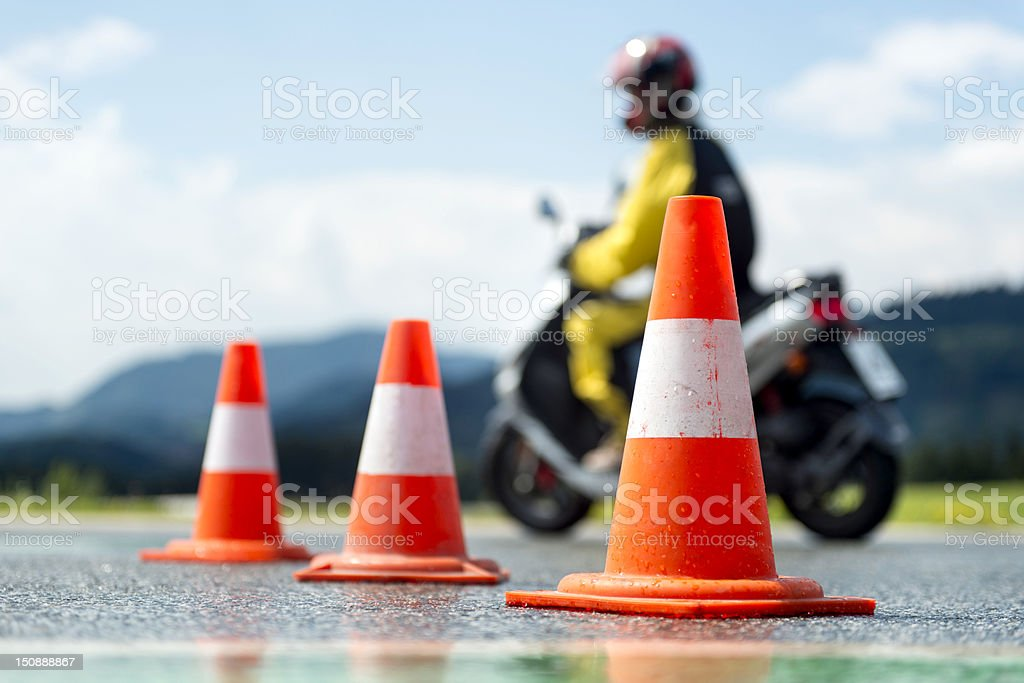 Low angle shot of traffic cones with a motorbike behind stock photo