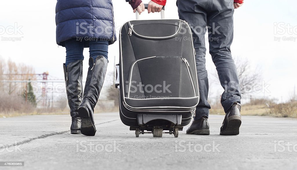Low angle view of a couple pulling suitcase stock photo