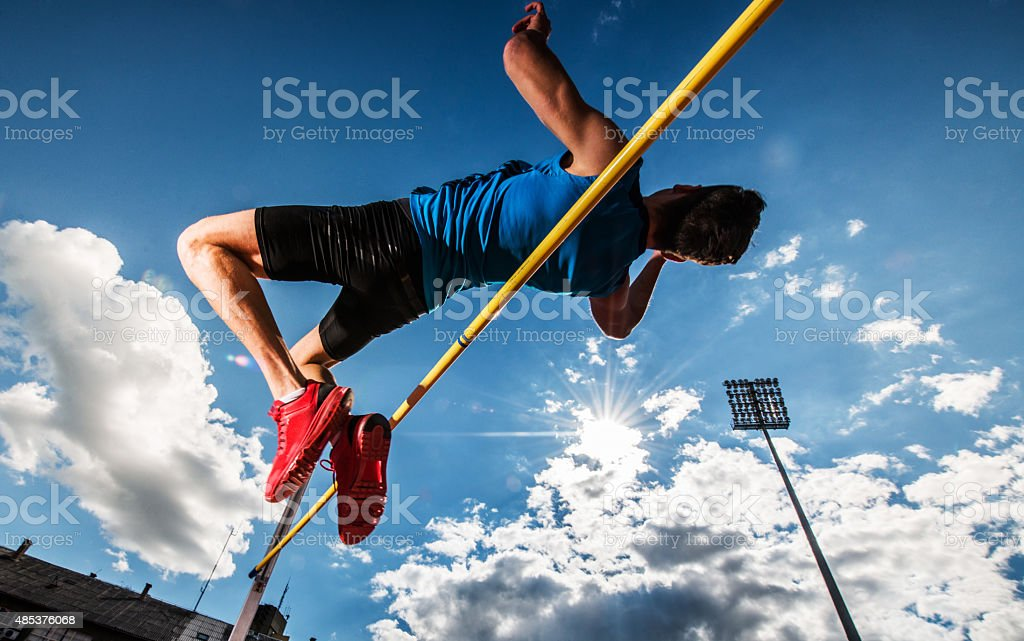 Low angle view of a young man performing high jump. stock photo
