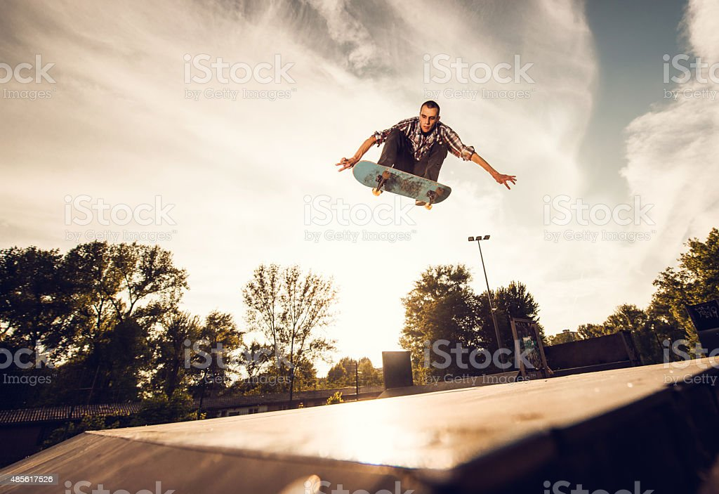 Low angle view of a young man skateboarding at sunset. stock photo