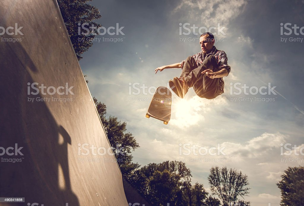 Low angle view of a young man skateboarding outdoors. stock photo