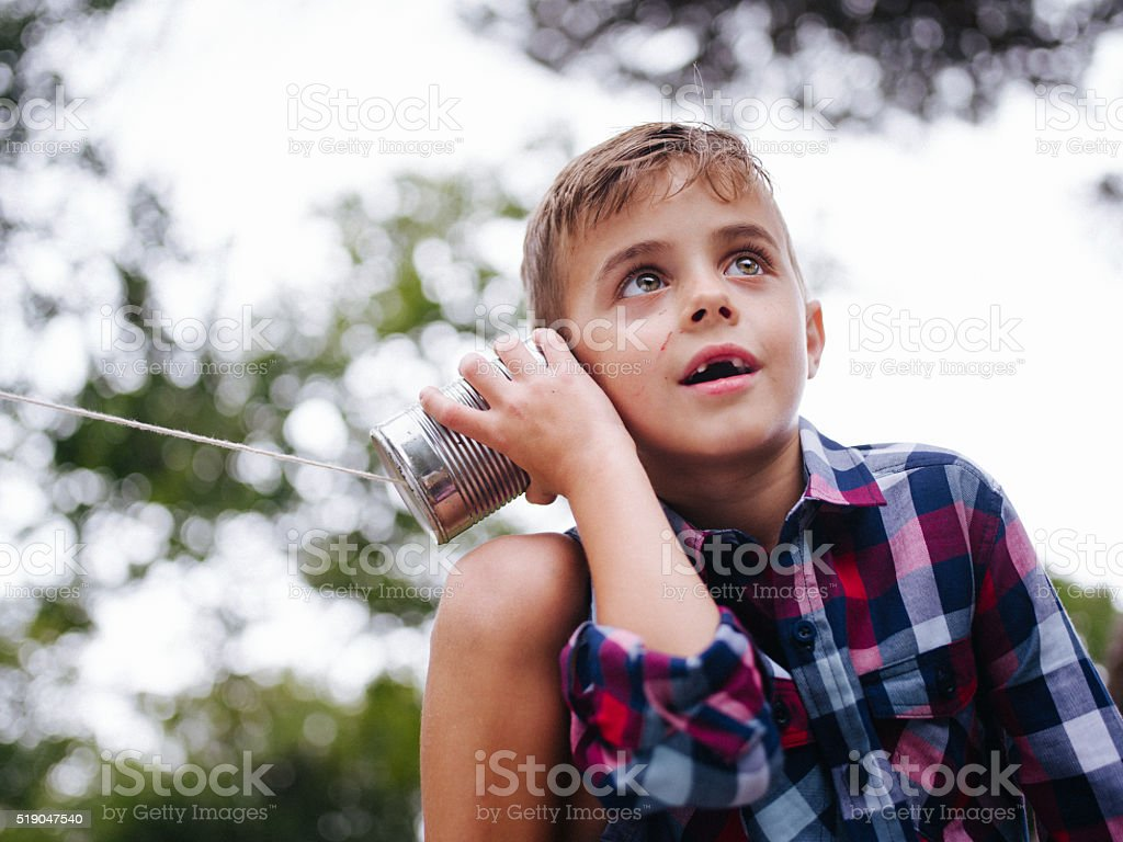 Low angle view of Boy listening on tin can phone stock photo