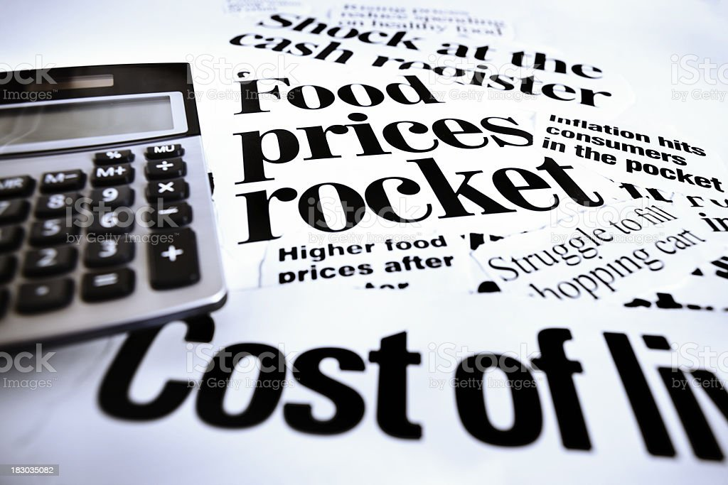 Low angle view of calculator and print headlines on inflation stock photo