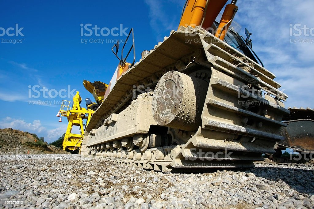 Low angle view of caterpillar tractor wheel on gravel royalty-free stock photo